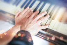Newly Wed Couple's Hands With Wedding Rings. Newlyweds Showing Their Wedding Rings On Piano