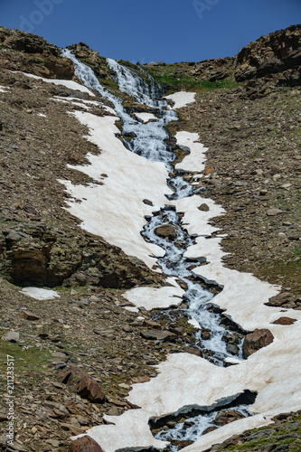 Fotografie, Obraz  Waterfall with ice and snowfields, vertical composition