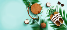 Round Rattan Bag, Coconut, Birkenstocks, Palm Branches, Sunglasses On Blue Background. Banner. Top View With Copy Space. Trendy Bamboo Bag And Shoes. Summer Fashion Flat Lay. Trip, Vacation Concept