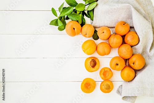fresh apricots scatter with green leaves on white wooden background with a table linen top view