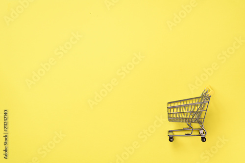 Photo  Shopping cart on yellow background