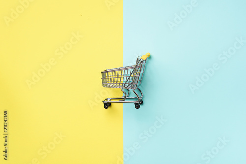 Fotografia Shopping cart on blue and yellow background
