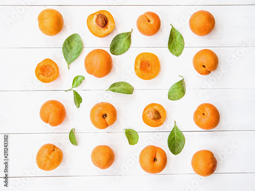 fresh apricot creative pattern in square on white wooden background with leaves flat lay top view