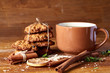 Christmas concept with a cup of hot tea, cookies and decorations on a log over wooden background, selective focus