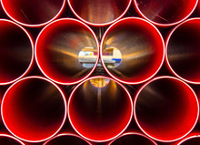 Stack Of Red Construction Pipes, The Symmetry Of Evenly Spaced Pipework Except For One Pipe Standing Out Slightly