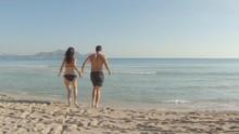 Young Couple Walking Through Shallow Sea On The Beach Of Majorca