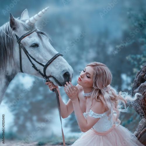 Wróżka w delikatnej sukni w stylu vintage przytula jednorożca. Fantastyczny, magiczny, promienny koń. Tło rzeka i las. Blondynka z falistymi włosami - lekki elf. Zdjęcie artystyczne