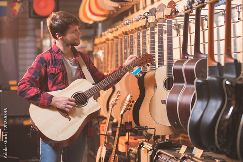 Tablou Canvas Young man with guitar in a music store