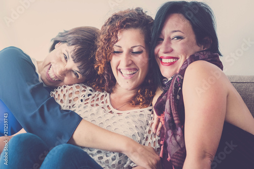Photo  cheerful females middle age young womane friends together sitting on a sofa at home in leisure activity indoor