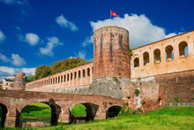 Pisa Ancient Walls Public Park With Bridge, Moat And Tower With Old City Red Flag Symbol Of The Medieval Republic