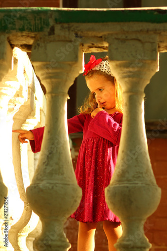 Fotografie, Obraz  Sunlit portrait of a cute toddler girl behind old balcony banisters