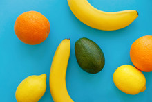 Bananas, Oranges, Avocado And Lemons On Bright Blue Paper, Trendy Flat Lay. Modern Summer Image Concept. Multi Fruit Flat Lay, Juicy Vitamin Abstract Background, Pop Art Style