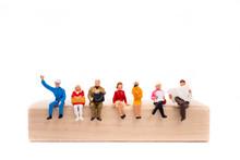Miniature People Sitting On Wo...