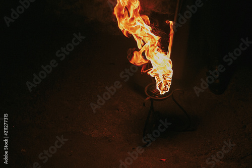 Fotografiet  burning torch with flames, amazing fire show at night at festival or wedding party