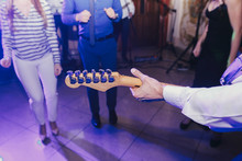 Musician Holding Guitar And Playing Live And Guests Having Fun And Dancing At Wedding Reception. Band Performing Acoustic Songs. People Dance At Party In Restaurant