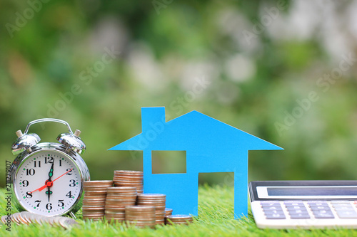 Fotografía  Mortgage calculator, Blue house model and stack of coins money with alarm clock
