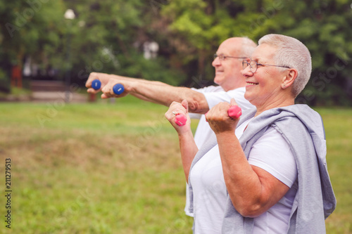Fotografie, Obraz  together we workout better - Smiling senior man and woman practice with dumbbells