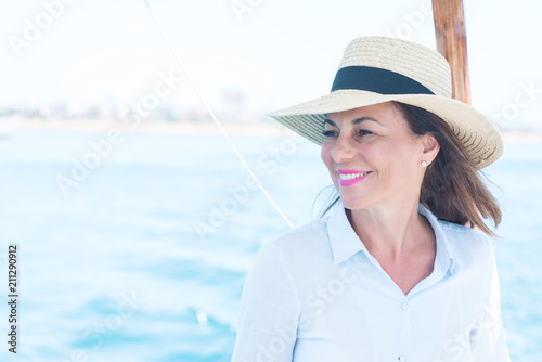 Beautiful middle age woman traveling on sailboat and smiling happy and confident Tableau sur Toile