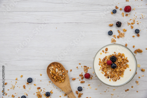 Canvas Prints Spices Bowl of yogurt with granola and fresh berries and wood spoon full whit granola on white wood table, background ,top view, copy space