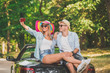 Fashionable couple sitting on the cabriolet trunk and taking self portrait.
