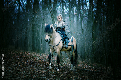Photo  Warrior Woman on a horse in the woods
