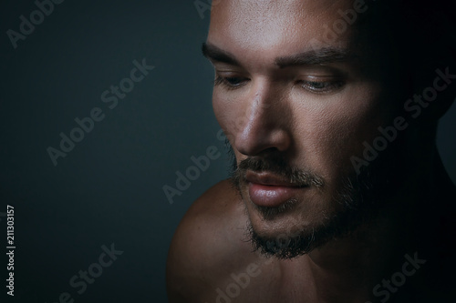 Close up portrait of a handsome young man with brave manly face on dark background. Caucasian man staring serious, male beauty, cosmetics.