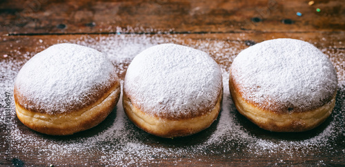 Leinwand Poster Krapfen with powder sugar, three and isolated on wooden background