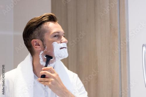 Fotografía  Reflection in a mirror of man shaving his face.