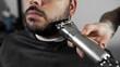 Tattoed barber shears the customer's beard by using trimmer at the barber shop, man's haircut and shaving at the hairdresser, barber at the shaving salon