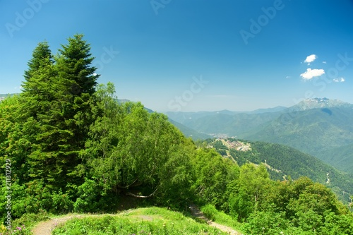 Tuinposter Blauw Mountain tourism. Green slope of the high big mountains. Alpine meadows in the Caucasus Mountains. Flowers and grasses. Beautiful blue sky and clouds.