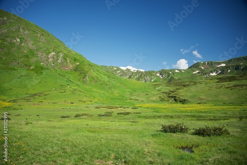 Foto op Aluminium Pistache Wide valley among the rocky peaks. Alpine meadows in the Caucasus Mountains. Flowers of all colors and grasses. Beautiful blue sky and clouds. Mountain tourism.