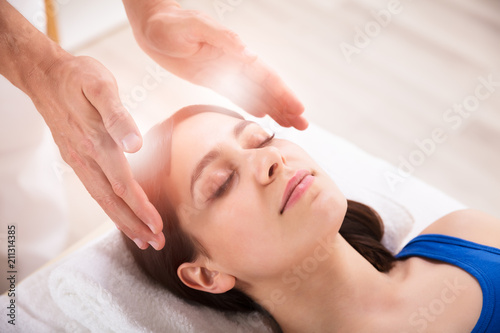 Therapist Performing Reiki Healing Treatment On Woman Wallpaper Mural