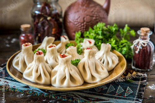 Georgian dumplings Khinkali with meat and red papper, on brown plate © qwasder1987
