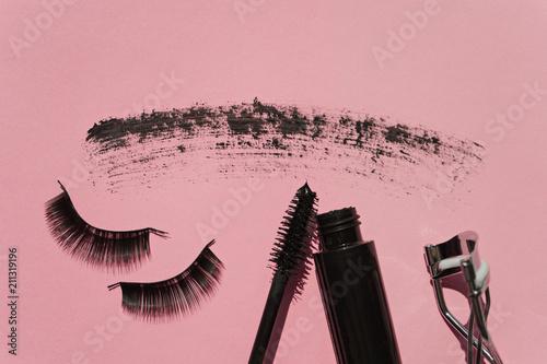 Black false lashes strips, mascara, curler on pink background Wallpaper Mural