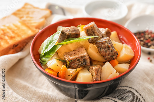 Poster Aromatische Bowl with tasty meat and potatoes on table
