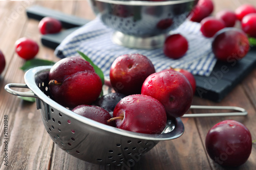 Colander with ripe juicy plums on table Wallpaper Mural