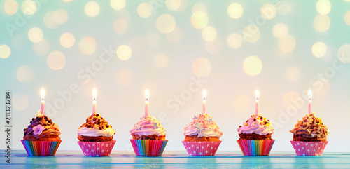 Fotografia  Row Of Colorful Cupcake With Candles And Bokeh Lights