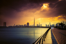 Sunset View Of Dubai Skyline With With Two Arab Men Taking A Walking At Promenade. UAE