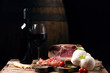 Bottle of wine with a glass on a table with rustic traditional italian food