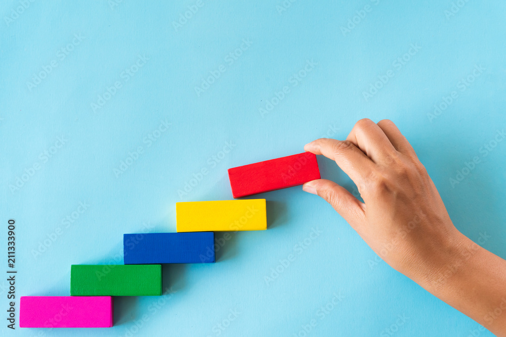 Fototapeta Concept of building success foundation. Women hand put red wooden block on colorful wooden blocks in the shape of a staircase