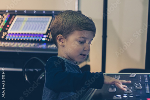 Fotografía  Little DJ adjusting sound on audio mixer in music studio.
