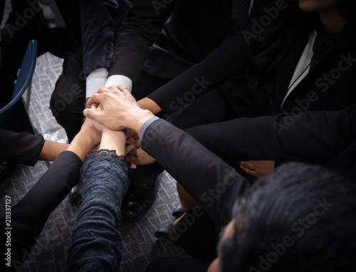 Close up top view of business people putting their hands together
