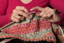 Close Up Of Hands Knitting A Fair Isle Pattern Hat.