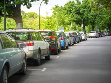 Many Cars Parked And Lined Up Under Trees On Urban Street. City Of Melbourne, VIC Australia.