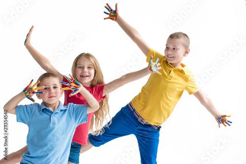 Fototapeta Three smiling kids with colourfull hands on white background obraz na płótnie