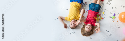 Fotografía  A girl and a boy lay on the white floor and play colorful air balloons on the bi