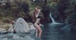 Young beautiful tourist visiting the Aling-Aling waterfall of the Bali island, Indonesia - video in slow motion