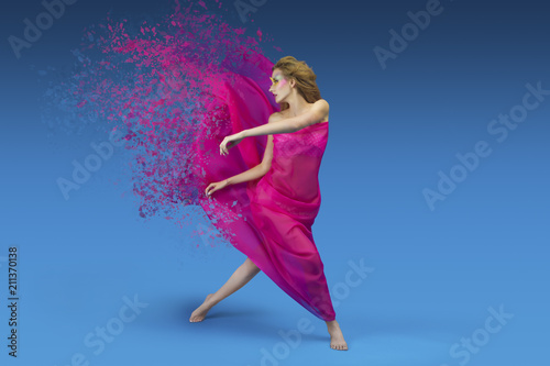 Photo Fashionable girl with ginger hair and bright make up posing / dancing with pink and silky fabric on blue background