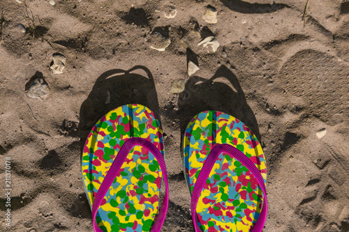 multicolored flip flops on sand with drawn heart shape. Consept of vacation