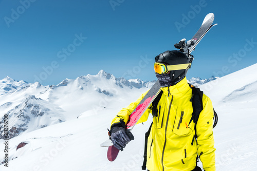A portrait of a skier in a protective helmet and glasses is a mask and scarf with skis on his shoulder in the snow-capped mountains of the Caucasus. Skiing,